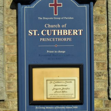 Noticeboard outside St Cuthbert's Church Princethorpe, 2019. Navy blue board attached to brickwork saying 'In Loving Memory of Dorothy Sutton 2008'. Also 'The Draycote Group of Parishes, Church of St Cuthbert, Priest in Charge Rev. Barbara Clutton' and contact details. | Image courtesy of Anne Langley