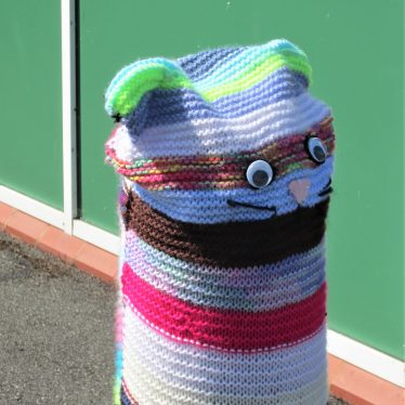 Multi-coloured knitted circles decorated at the top by a cat face | Anne Langley