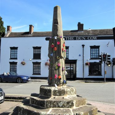 Stone obelisk standing on top of octagonal steps, decorated with knitted flowers. Dun Cow pub behind | Anne Langley