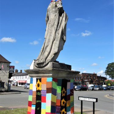 Statue with knitted bobble hat, scarf and plinth with colourful knitting spelling out '100 years of WI' | Anne Langley