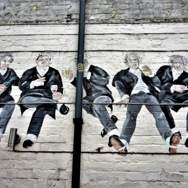 Row of 5 lawyers in wigs seated and drinking glasses of beer or wine, on white brick wall | Image courtesy of Anne Langley