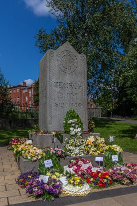 The George Eliot memorial in Nuneaton, June 2019. Stone memorial engraved 'GEORGE ELIOT 1819-1880' with a laurel wreath and a number of colourful floral tributes around the base | Image courtesy of Steve Simmonds
