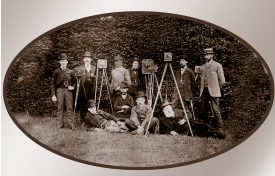 10 gentlemen smartly dressed with cameras on tripods standing (and reclining) in front of an ivy-clad wall | Image courtesy of Edwin Walker