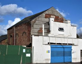 Former Primitive Methodist Chapel then Plaza Cinema, King Street Bedworth, 2020. Red brick building with three round-headed bricked up windows on the side, white-painted entrance (with roll-up blue door) added at the front and brick extension at the rear | Image courtesy of Anne Langley