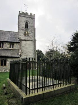 Flat tombstone with inscription surrounded by iron railings; church with tower behind   Image courtesy of Anne Langley