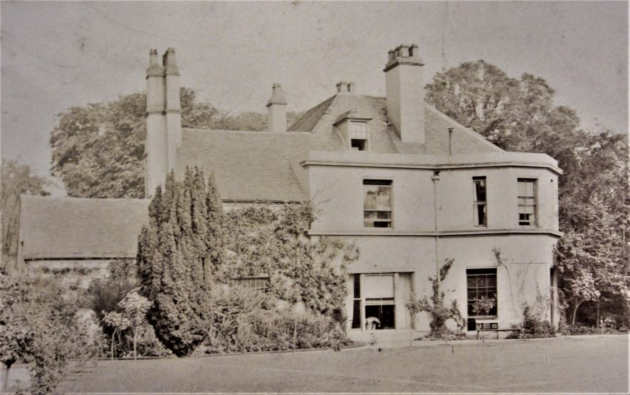 Postcard of Tiddington House, 1909. Black & White photo of 2-storey Georgian house (plus attic dormer window in roof) with open sash windows. Lawn and garden with shrubs in front and trees behind | Warwickshire County Record Office reference PH 352/5/26