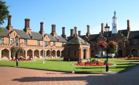 Nicholas Chamberlain's Hospital at Bedworth, 2007. Red brick 2-storey U-shaped building with arcade below, crennelations, slate roof with tall chimneys and central white clock tower. Formal garden with lawn and bedding surrounding small brick well-house in the centre of the courtyard | Image courtesy of Anne Langley