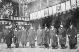 Brethren at Lord Leycester's Hospital, 1900s. Nine Brethren in gowns (with medals) and top hats in courtyard with gallery above, four shields with coats of arms and a porcupine | Warwickshire County Record Office reference PH352/187/39