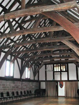 The Great Hall of Lord Leycester's Hospital, Warwick. Interior of hall showing fine timber roof springing from stone wall; timber framed partition at one end with shield with coat of arms; row of modern chairs | Image courtesy of Anne Langley