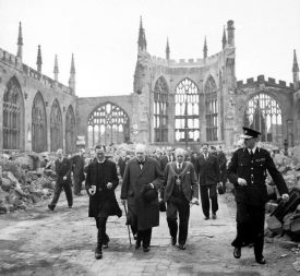 Winston Churchill walking through the ruined nave of Coventry Cathedral, after it was severely damaged in the Coventry Blitz of 14–15th November 1940 | Image taken by Capt Horton, War Office official photographer, Courtesy of Imperial War Museum. H_14250 Imperial War Museum Archives