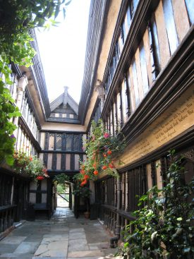 Ford's Hospital courtyard Coventry, 2007. Stone-flagged narrow courtyard of timber-framed building with jetted upper stories; hanging baskets; rules written on wall | Image courtesy of Anne Langley