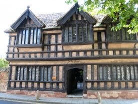 Ford's Hospital exterior Coventry 2007. Timber-framed building with stone footplate, central doorway, jetted upper storey, carved wooden gables and diamond-paned windows. | Image courtesy of Anne Langley
