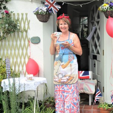 Woman on her doorstep with turban and apron with old advert for tea over union jack dress; table with lace tablecloth laid for tea | Anne Langley
