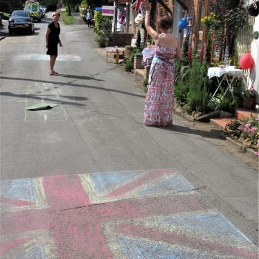 Bunting and flags; road with chalked Union Jack, hopscotch grid and rainbow thanking the NHS; tea tables set outside cottages | Anne Langley