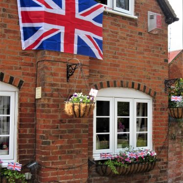 Large union jack attached to the side of a house and small union jacks planted in window boxes and a hanging basket | Anne Langley