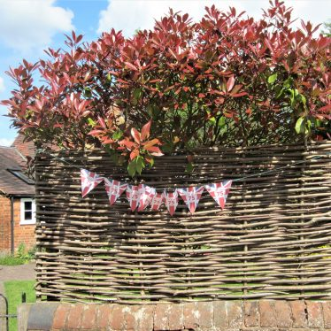 String of bunting union jack flags (with 75 superimposed) attached to a hurdle fence | Anne Langley