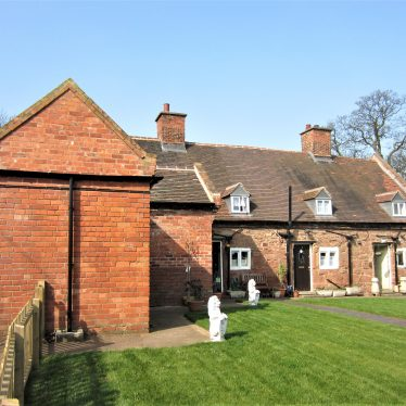 Red brick one-storey building joined at right-angles to row of 3 stone cottages with gable windows in tiled roof. Lawn in front with two white stone lions | image courtesy of Anne Langley