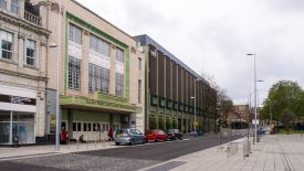 The Ellen Terry Building, formerly the Odeon Cinema, Coventry. An art deco frontage with green decoration, a brick building adjoins it. | Image oriignally uploaded by Ed Webster to flickr