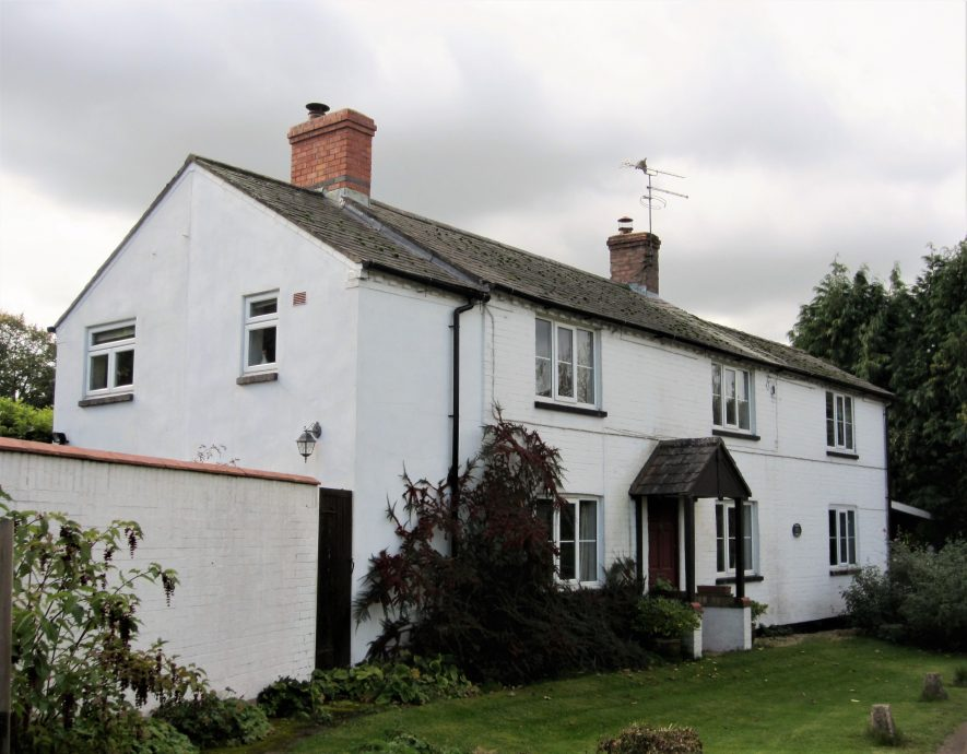 2-storey, white painted cottage with slate roof, porch and two chimneys   Image courtesy of Anne Langley