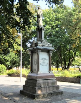 Starley statue of Fame erected 1884 in Coventry. Granite & marble base with Fame on top; 'James 1884 Starley' written on one face and a tricycle on another. It stands on a pavement with trees in parkland behind | Image courtesy of Anne Langley