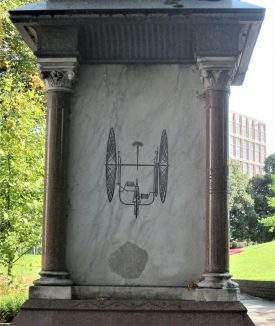 Marble base of a statue with etching of an early tricycle; park with trees and lawn behind | Image courtesy of Anne Langley