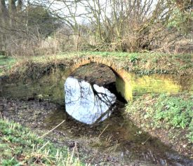 Red brick bridge over stream with woodland behind | Image courtesy of Anne Langley