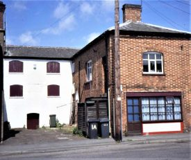 L-shaped 2-3-storey brick building with slate roof; some windows boarded up; small shop fronting onto main street   Image courtesy of Anne Langley