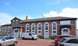 Brotherhood House, Rugby, 2021; formerly Baptist Chapel and then community centre. Red brick building with stone dressings and slate roof, round-headed windows and 2 entrance doors, fenced off | Image courtesy of Anne Langley