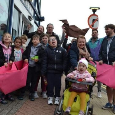 Conny Art Festival - giant origami boat race facilitated by Lady Kitt, 2019. Colour photo, exterior. A group of around 14 people, stand by a road looking towards the camera. Members of the group are holding two bright pink, giant origami boats. The people are variety of ages and ethnicities, many are smiling. At the front of a group, a toddler in a green buggy grins excitedly.   Image courtesy of Elain Robertson