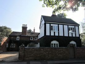 2-storey L-shaped building of red brick with tall chimneys and timber framing on part of the upper storey   Image courtesy of Anne Langley